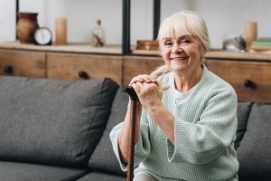 cheerful senior woman sitting on sof
