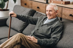 smiling retired man sitting on sofa