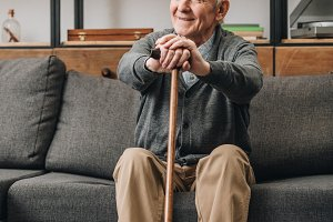 cheerful pensioner smiling and holdi