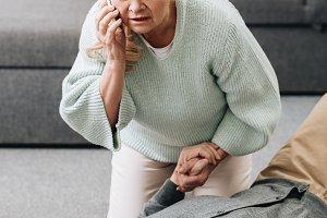 senior woman helping old husband who