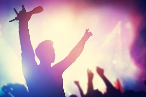 Excited singer raising hands on stag
