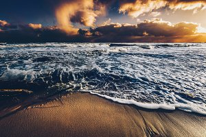 Sea waves on a sandy shore at sunset