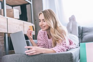smiling woman holding credit card wh