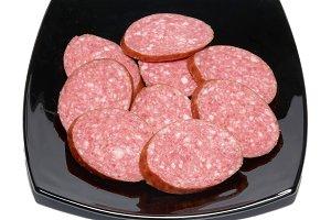 Sliced sausage on black plate