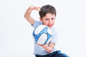 A young boy with a football ball