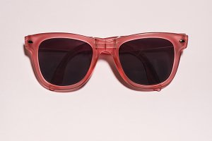 Red bright sunglasses on a pastel pi