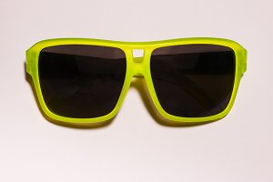 Green bright sunglasses on a pastel