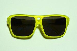 Green bright sunglasses on a pastel