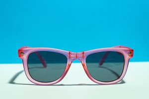 Pink bright sunglasses on a pastel b