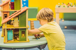 Boy playing with wooden house in