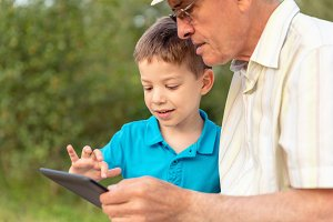 Child and senior man using a tablet