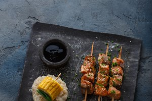 Salmon kebabs with corn and noodles