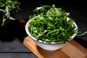 Fresh rocket salad in bowl on the wo