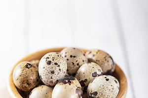 quail eggs in wooden plate over whit
