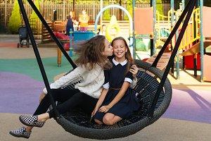 Sisters ride on swing. Leisure.