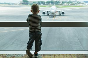 In airport child looks at the plane