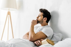 young thoughtful man lying in bed wi