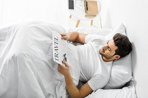 handsome man reading travel newspape