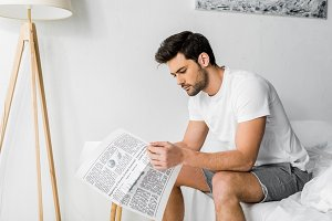 handsome young man reading newspaper