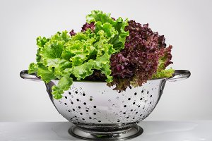 Fresh lettuce in a metal colander.