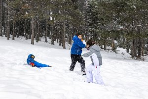 Three kids playing with a snow balls