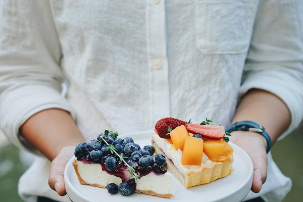 Hands holding plate of fruit pie
