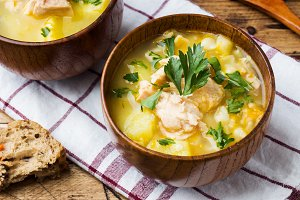 Fish soup in a wooden bowl