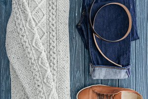 Flat lay with knitted sweater, denim