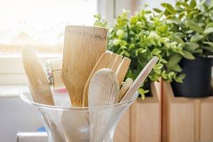 Wooden kitchen utensils in a glass c