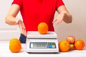 woman weighting fruints on digital w