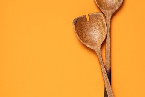 Wooden serving spoons on colorful ba