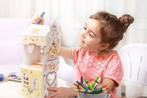 Cute little girl is painting a house
