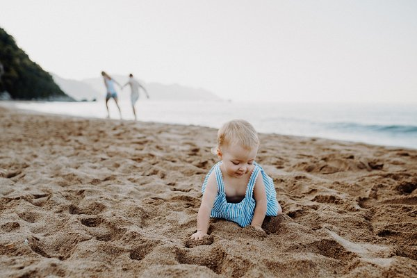 People Images: HalfPoint - A small toddler girl playing in sand