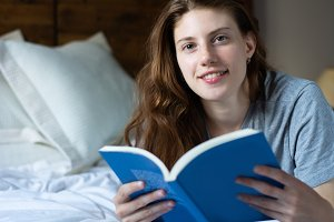 woman laying in bed and reading book