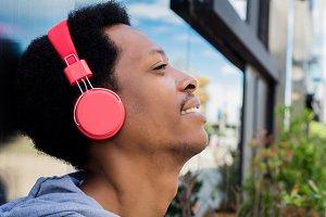 Young man enjoying music outdoor.