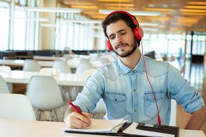 Young male student studying in the l