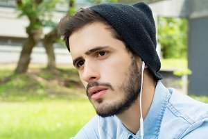 Young man listening to music with ea