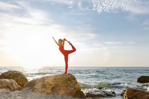 A woman in a red suit practicing yog