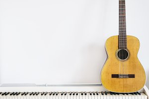 Acoustic guitar on piano keyboard in
