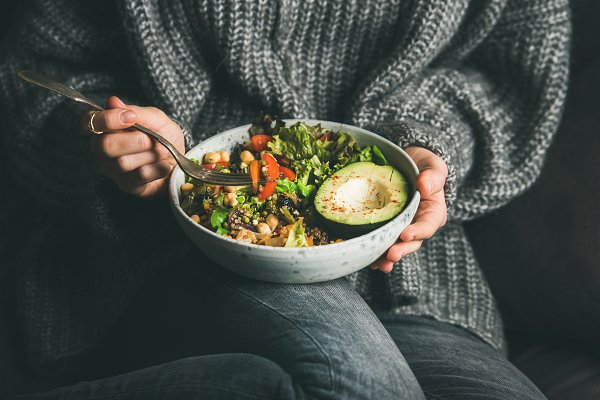 Woman in sweater eating fresh salad