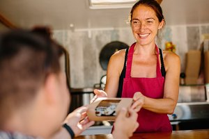 Cheerful woman selling sushi to man