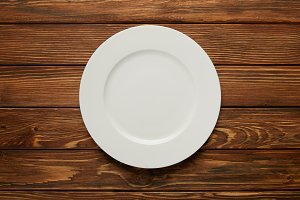 top view of white empty plate on woo