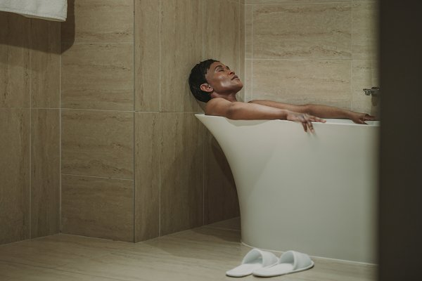 Mature african woman lying in bath