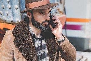 Bearded Man in hat talking on a