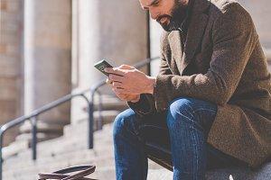 Adult Bearded Man using smartphone