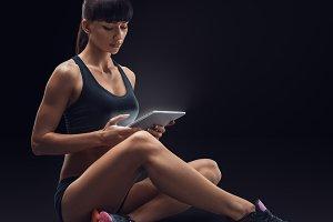 Fitness woman using a digital tablet