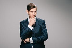 pensive businessman in suit standing