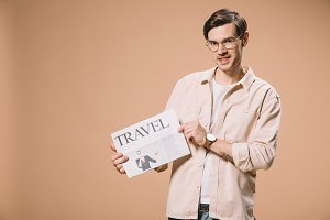 smiling man holding travel newspaper