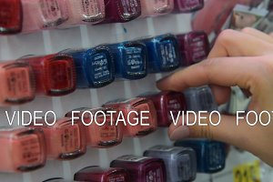 Woman buying nail polish in the