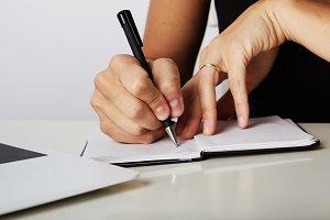 Beautiful Female hands write pen in